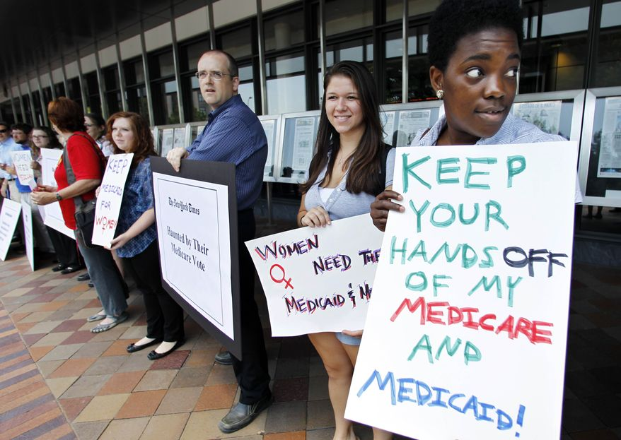 ** FILE ** In this June 13, 2011, file photo Dena Robinson, from right, and Hannah Hoffman, join dozens of Medicare advocates gathered outside the Newseum in Washington. (AP Photo/Manuel Balce Ceneta, File)