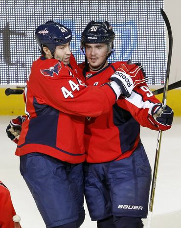 Washington Capitals defenseman Roman Hamrlik (44) congratulates center Marcus Johansson after he scored on Ottawa Senators goalie Alex Auld (35) during the first period of an NHL hockey game in Washington, Saturday, Oct. 15, 2011. (AP Photo/Ann Heisenfelt)