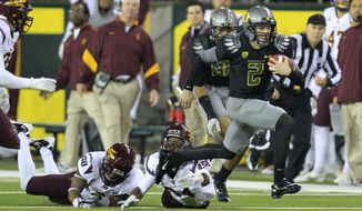 Oregon's Bryan Bennett eludes Arizona State defenders during the second half of the Ducks' 41-27 win over the No. 18 Sun Devils. Oregon improved to 51. (Associated Press)