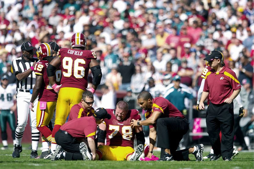 Redskins offensive lineman Kory Lichtensteiger is tended to after suffering a knee injury during the first quarter against Philadelphia. He reportedly tore his ACL and MCL. (Andrew Harnik/The Washington Times)