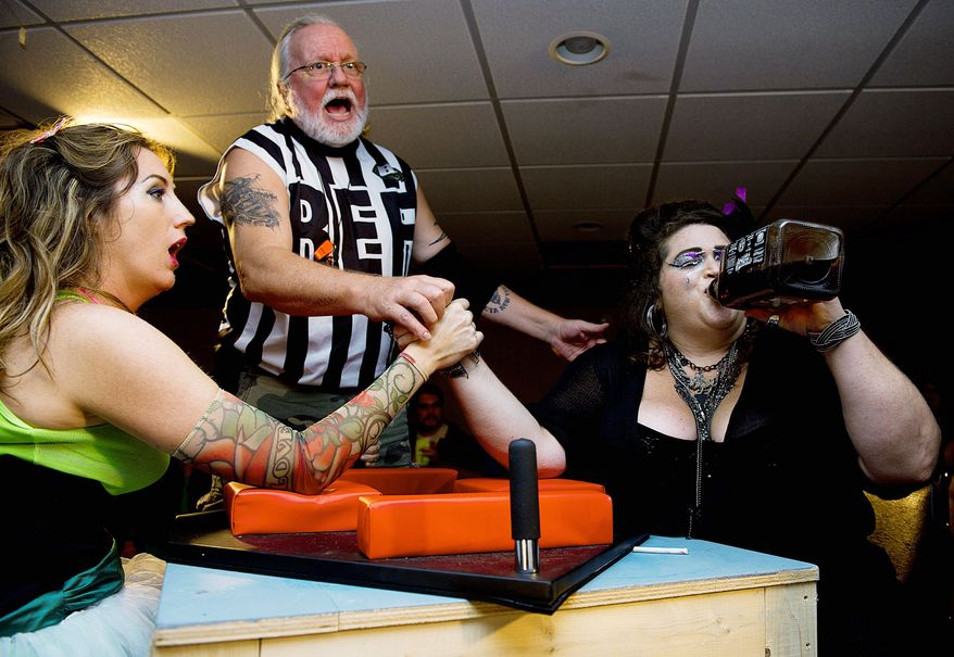 "Referee Philip Yunger reacts as ""Scarlett O'Scara,"" aka Ann Marie Wilson (left) of Silver Spring, and ""Amy Smackhouse,"" aka Andrea Kavanagh of the District, prepare to arm-wrestle during the D.C. Lady Arm Wrestlers league event. The arm-wrestling competitions raise money for charity. (Barbara L. Salisbury/The Washington Times)"