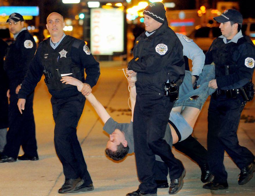 Chicago police carry away a protester early Sunday. Police arrested 175 people protesting what they called corporate greed after they refused to take down their tents and leave Grant Park when it closed Saturday night. (Associated Press)
