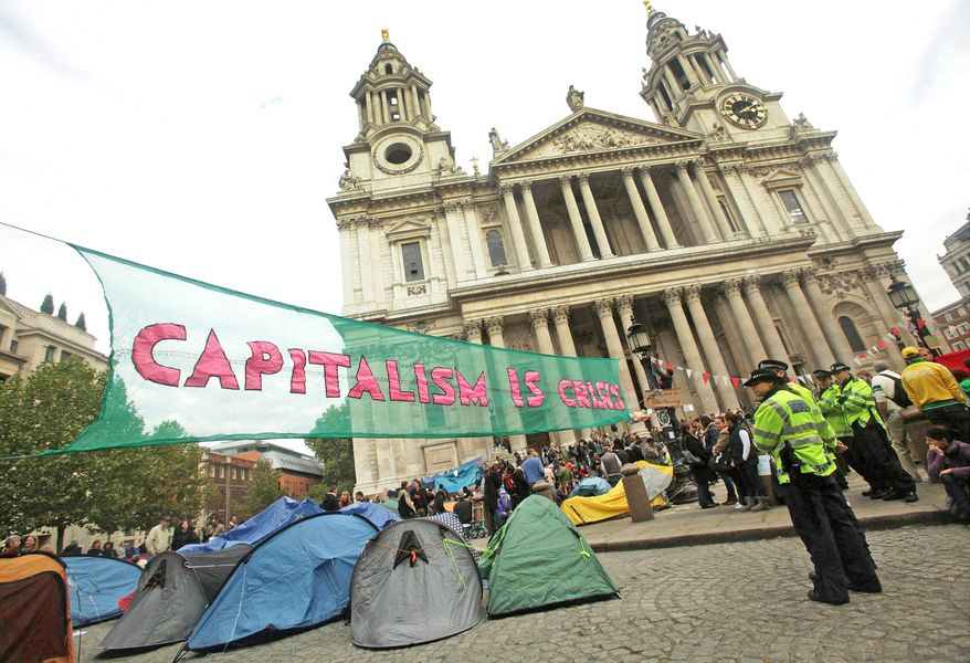 Police look on as protesters, who are part of the Occupy London Stock Exchange demonstration, continue their demonstration outside St Paul's Cathedral in London on Sunday. There were also protests in Rome and Amsterdam. (Associated Press)