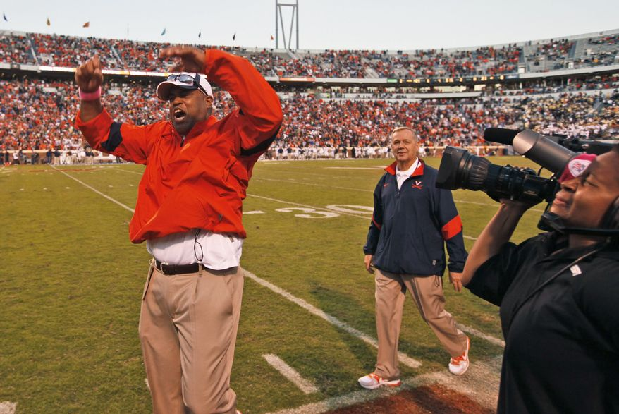 Virginia head coach Mike London celebrates his team' 24-21 win over No. 12 Georgia Tech  at Scott Stadium in Charlottesville, Va. on Saturday, Oct. 15, 2011. (AP Photo/Steve Helber)