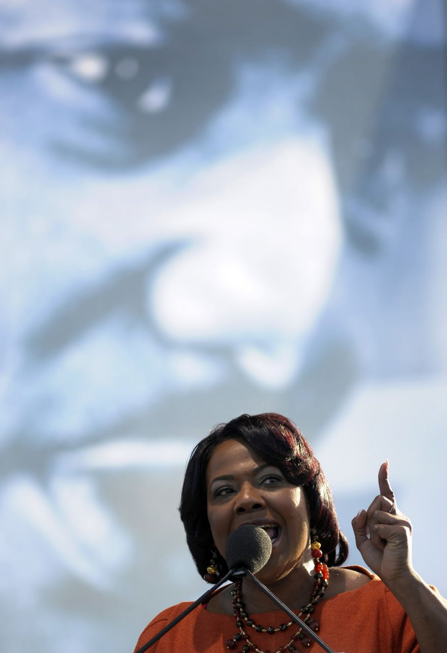 Standing under an image of her father, Martin Luther King Jr., the Rev. Bernice King speaks at the dedication of the memorial to him in Washington on Sunday, Oct. 16, 2012. (AP Photo/Cliff Owen)