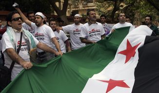 Protesters carry a Syrian flag during a demonstration against President Bashar Assad in front of the Syrian Embassy in Cairo on Saturday, Oct. 15, 2011. (AP Photo/Mohammed Abu Zaid)