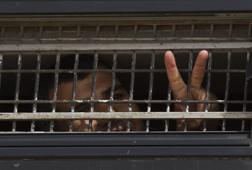 On Sunday, Oct. 16, 2011, a Palestinian prisoner flashes a V-sign on board an Israeli Prison Service bus transferring Palestinian prisoners who are to be exchanged for captured Israeli Sgt. Gilad Schalit. (AP Photo/Ariel Schalit)