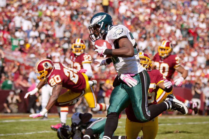 Washington Redskins Josh Wilson (26) tackles Philadelphia Eagles LeSean McCoy (25) after picking up 21 yards and setting the Eagles up for their second touchdown during the first quarter. (Pratik Shah / The Washington Times)