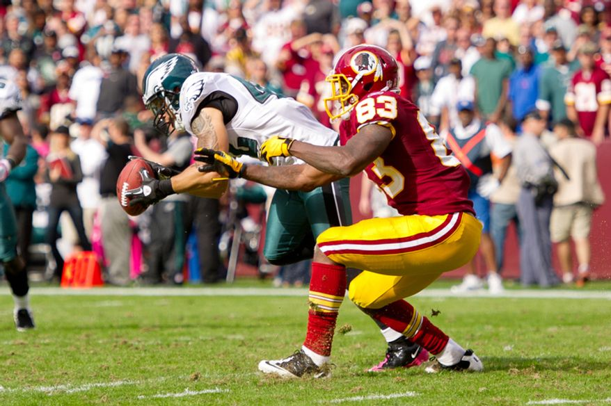 A pass intended for Washington Redskins Fred Davis (83) is intercepted by Philadelphia Eagles Kurt Coleman (42) and run back 24 yards during the third quarter. (Andrew Harnik / The Washington Times)