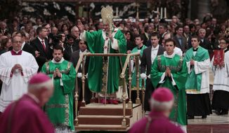 ** FILE ** Pope Benedict XVI leaves St. Peter's Basilica on a mobile platform at the end of a Mass at the Vatican on Sunday, Oct. 16, 2011. (AP Photo/Gregorio Borgia)