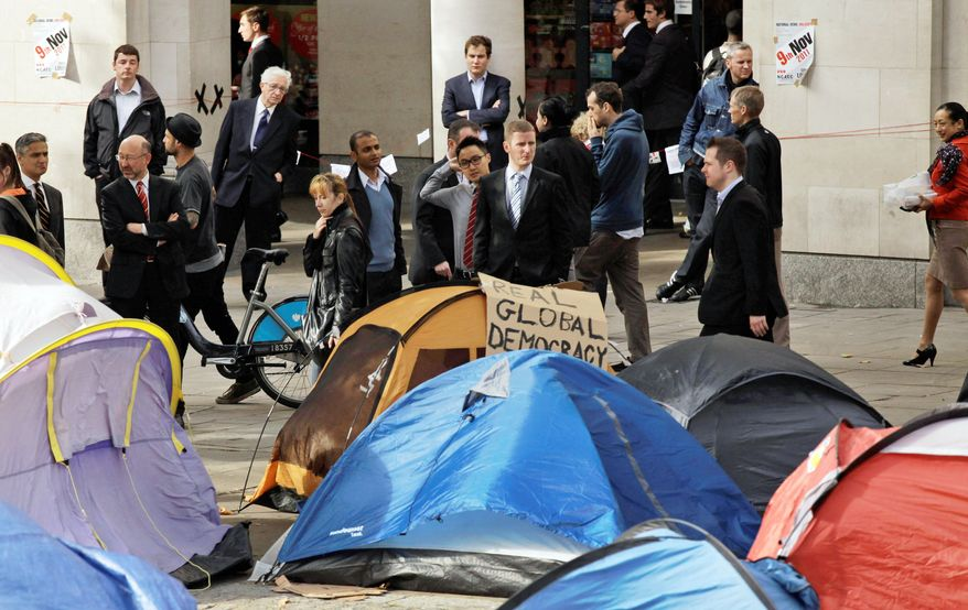 """Business people, taking a break during their lunch hour on Monday, look at tents put up by protesters from the """"Occupy London Stock Exchange"""" group as they continue their demonstration that started on Saturday outside St. Paul's Cathedral near the London Stock Exchange. (Associated Press)"""