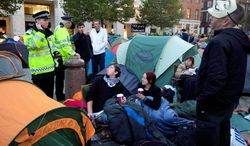 Police officers chat with protesters in a tent city in London on Monday. (Associated Press)