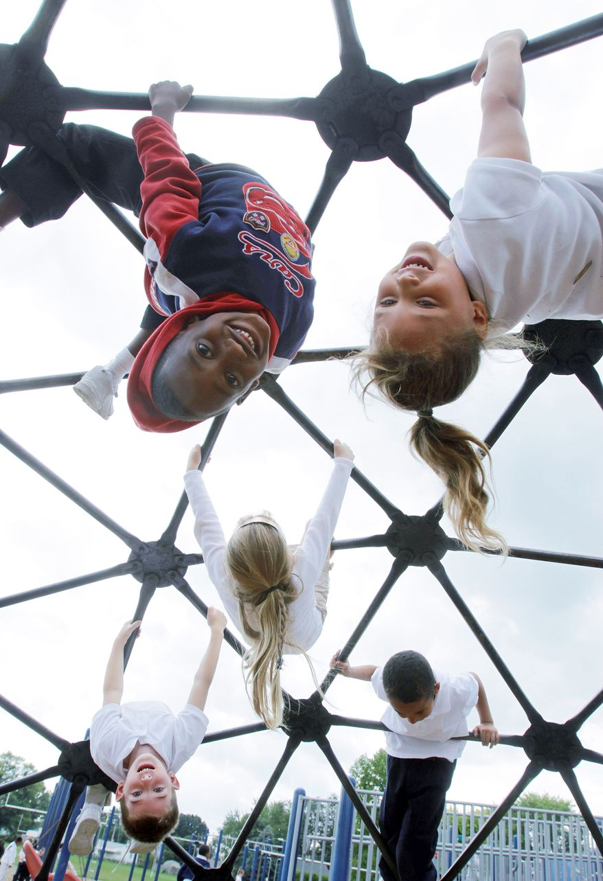 ** FILE ** Students at Northeast Elementary Magnet School in Danville, Ill., enjoy the playground during a physical education class. (Associated Press)