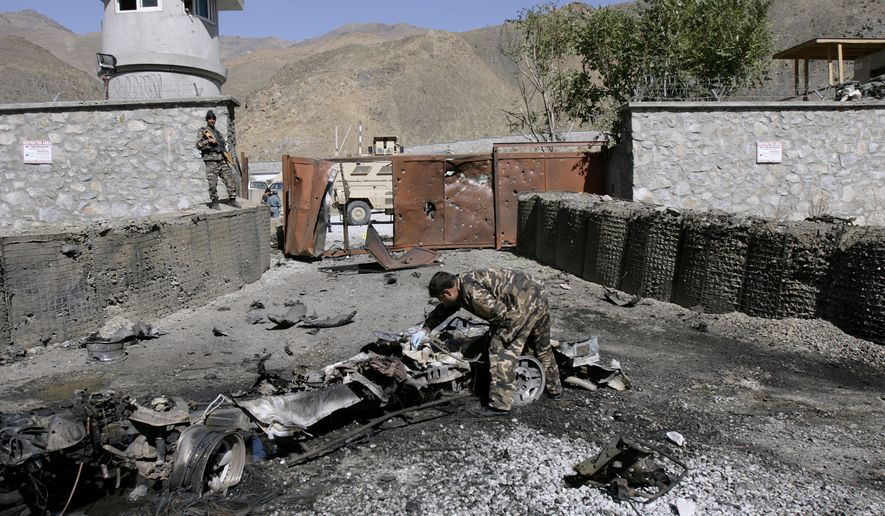 An Afghan security officer (center) collects evidence from the site of an attack by militants at the gate of an American base in Panjshir, north of Kabul, Afghanistan, on Saturday, Oct. 15, 2011. Militants tried to blast their way into the base before dawn with rocket-propelled grenades and a vehicle packed with explosives. All four of the attackers were killed, and two Afghan security guards were wounded. (AP Photo/Ahmad Jamshid)