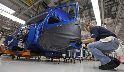**FILE** Shelby Corvin installs a door handle on a truck cab on the Volvo truck assembly line at the Volvo plant in Dublin, Va., on Jan. 26, 2011. (Associated Press)