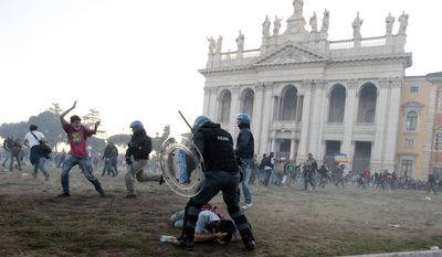A police officer subdues a protester in front of the Basilica of St. John Lateran in Rome on Saturday, Oct. 15, 2011. (AP Photo/Gregorio Borgia)