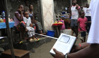 Liberians listen to the announcement of election results on a portable radio in the 19th Street area of Sinkor, Monrovia, Liberia, on Friday, Oct. 14, 2011. (AP Photo/Rebecca Blackwell)