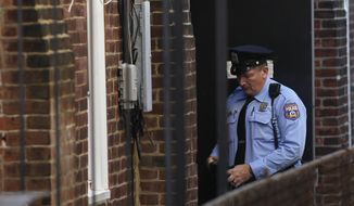 A police officer stands in an alley doorway of an apartment building in Philadelphia on Monday, Oct. 17, 2011,  after the landlord on Saturday discovered four mentally disabled adults locked in the sub-basement of the building. (AP Photo/Matt Rourke)