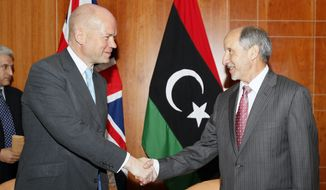 British Foreign Secretary William Hague (left) shakes hands with Libyan interim leader Mustafa Abdul-Jalil, the head of the governing National Transitional Council, in Tripoli, Libya, on Monday, Oct. 17, 2011. (AP Photo/Abdel Magid al-Fergany)