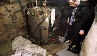 Sgt. Joseph Green observes the dank boiler room in Philadelphia where four mentally disabled adults were found locked inside Saturday. (Associated Press)