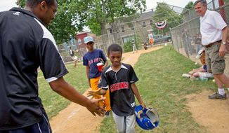 Akinlabi Mason greets his younger son Elijah, 8, after he scored a run as his older son Paul, 9, looks on during a Capitol Hill Little League game in June at Daniel A. Payne Elementary School in Washington. (Rod Lamkey Jr./The Washington Times)
