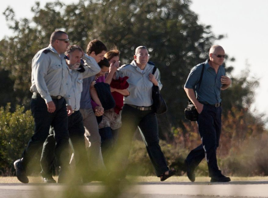 Noam Schalit, right, and Aviva Schalit, third right, parents of Israeli captured soldier Gilad Schalit walk together with their son Yoel, fifth right, and his girlfriend Yaara Winkler, fourth right, along with Israeli army officers towards an Army helicopter, not seen, in Tefen, northern Israel, Tuesday, Oct. 18, 2011.  (AP Photo/Ariel Schalit)