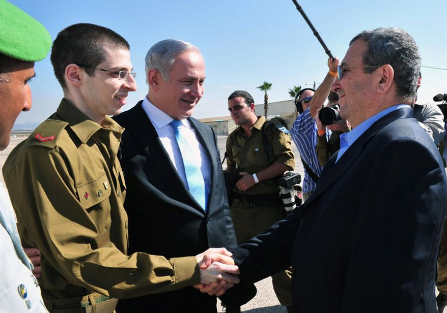 Released Israeli soldier Gilad Schalit, left, shakes hand with Defense Minister Ehud Barak as Israeli Prime Minister Benjamin Netanyahu, center, smiles at the Tel Nof Air base in southern Israel, Tuesday, Oct. 18, 2011.  (AP Photo/ Defense Ministry, Ariel Hermoni, HO)