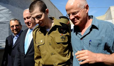 Released Israeli soldier Gilad Schalit, is escorted by his father Noam Schalit, right, Prime Minister Benjamin Netanyahu and Defense minster Ehud Barak as he arrives at Tel Nof Air base in southern Israel, Tuesday, Oct. 18, 2011.  (AP Photo/ GPO, HO)