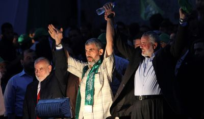"""Freed Palestinian prisoner Palestinian Yehiye Sinwar, a founder of Hamas' military wing, center, is greeted by Gaza's Hamas Prime Minister Ismail Haniyeh during a rally celebrating the release of Palestinian prisoners in Gaza City, Tuesday, Oct. 18, 2011. Sinwar, a founder of Hamas' military wing, told the crowd that Palestinian militant groups must win freedom for the remaining prisoners by """"all necessary means. Sinwar, among those freed Tuesday, had been sentenced to life for his role in the abduction and killing of two Israeli soldiers in the 1980's. He stopped short of calling for new abductions in his speech, but did so in interviews earlier in the day. (AP Photo/Adel Hana)"""