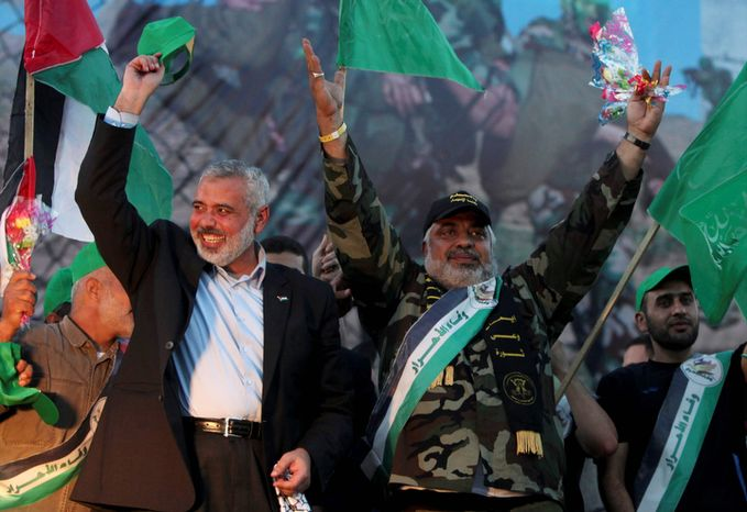 Gaza's Hamas Prime Minister Ismail Haniyeh, left, stands with released Palestinian prisoner Mohammed Al Hasani, center, among others as they celebrate during a welcoming ceremony, in Gaza City, Tuesday, Oct. 18, 2011.  (AP Photo/Tara Todras-Whitehill)