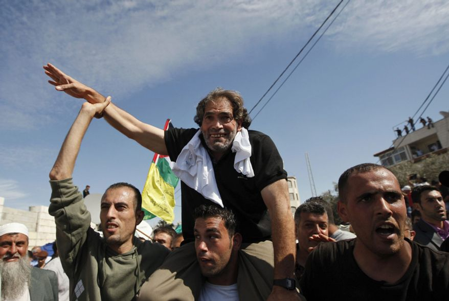 Released Hamas militant Fakhri Barghouti waves to the crowd after arriving in the West Bank city of Ramallah, Tuesday, Oct. 18, 2011. The Hamas militant group released an Israeli soldier Tuesday more than five years after his capture, turning him over to Egyptian mediators in exchange for hundreds of Palestinian prisoners. Sentenced to life for killing an Israeli, Barghouti had spent 34 years in prison, making him one of the longest-serving inmates. (AP Photo/Majdi Mohammed)