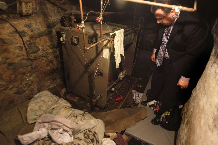 On Monday, Oct. 17, 2011, Philadelphia police Sgt. Joseph Green investigates the dank basement room where four weak and malnourished mentally disabled adults, one chained to the boiler, were found on Saturday. (AP Photo/Ron Cortes, Pool)