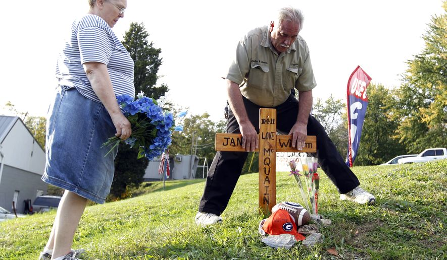 Charlene and Charles Barnes plant a cross and flowers with the names of Jane and William McQuain at the side of the road in Clarksburg, Md., on Tuesday Oct. 18, 2011, where Maryland police found remains that they believe are those of a missing boy whose mother was discovered slain. (AP Photo/Jose Luis Magana)