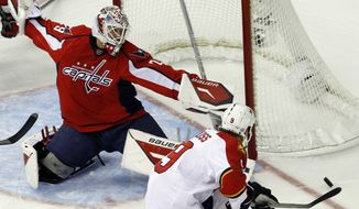 Washington Capitals goalie Tomas Vokoun, left, of the Czech Republic, deflects a shot by Florida Panthers center Stephen Weiss (9) during the first period of an NHL hockey game in Washington, Tuesday, Oct. 18, 2011. (AP Photo/Ann Heisenfelt)