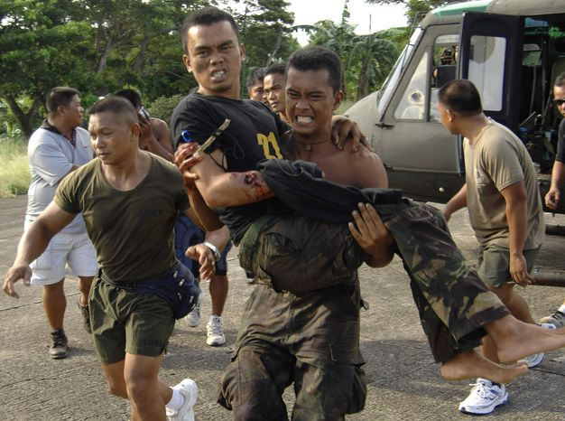 A Filipino soldier carries a wounded trooper from Basilan province as they land at the southern port city of Zamboanga, Philippines, on Tuesday, Oct. 18, 2011. Philippine troops battled Muslim guerrillas in fierce fighting in volatile Basilan province. (AP Photo/Al