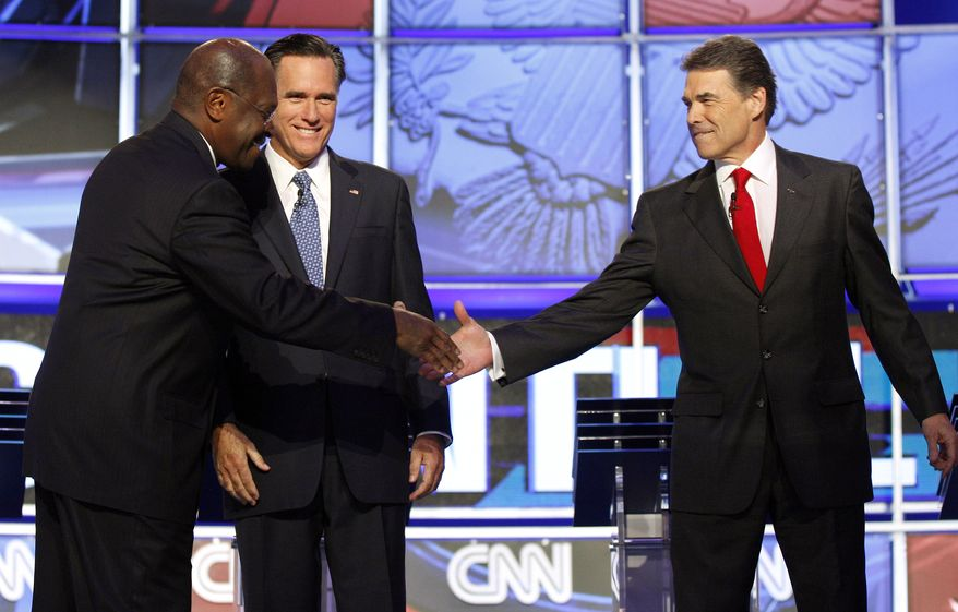 Republican presidential candidates Herman Cain, left, shakes hands with Texas Gov. Rick Perry, right, as former Massachusetts Gov. Mitt Romney looks on before a Republican presidential debate Tuesday, Oct. 18, 2011, in Las Vegas. (AP Photo/Isaac Brekken)