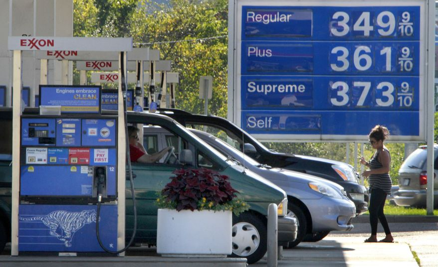Vehicles line up at the pumps at an Exxon minimart in Carnegie, Pa., on Tuesday, Sept. 27, 2011. (AP Photo/Gene J. Puskar)