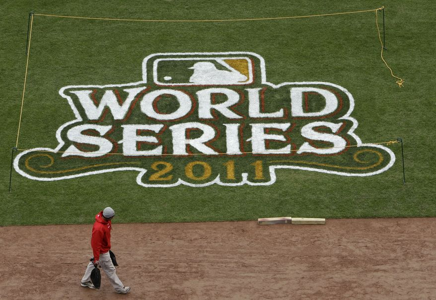 A worker is seen along the first base line before practice for Game 1 of baseball's World Series between the St. Louis Cardinals and the Texas Rangers Tuesday, Oct. 18, 2011, in St. Louis. (AP Photo/Paul Sancya)