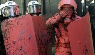 Greek riot police officers, covered in red paint thrown by protesters, react during clashes in central Athens on Wednesday. Anger over new austerity measures and layoffs erupted into violence, as demonstrators hurled chunks of marble and gasoline bombs and riot police responded with tear gas and stun grenades. (Associated Press)