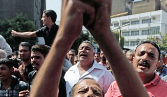 A man who lost a relative as Copts and Egyptian troops clashed on Oct. 9 holds a cross Oct. 10 in front of the Cairo morgue. (Associated Press)