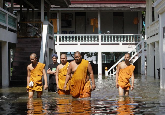 Thai Buddhist monks wade through Ban Kadee temple in Pathum Thani province, north of Bangkok, on Wednesday. Thai authorities were staging a fighting retreat Wednesday against floodwat