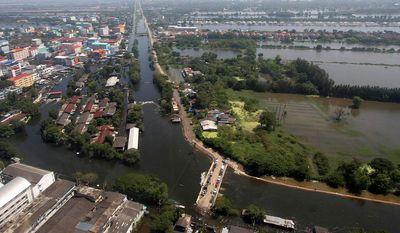 Water from Rangsit canal overflows in an area in Pathum Thani province, central Thailand, on Wednesday. (Associated Press)
