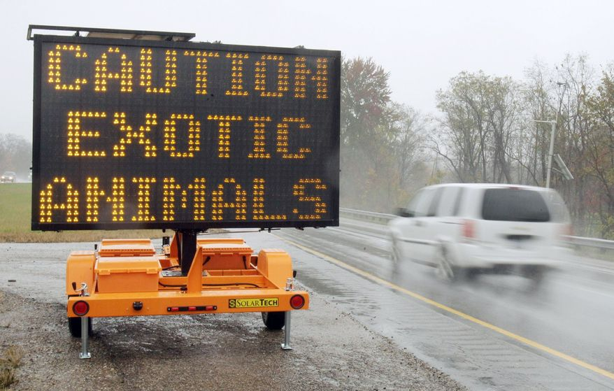 A sign warning motorists that exotic animals are on the loose stands along I-70 near Zanesville, Ohio. A wolf and a monkey were still unaccounted for after sheriff's deputies hunted down and shot nearly 50 other wild animals that were apparently freed by their owner. (Associated Press)