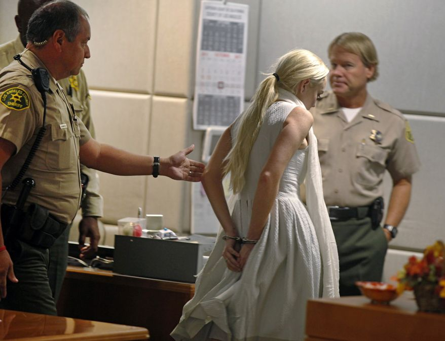Los Angeles County deputy sheriffs take actress Lindsay Lohan into custody after a judge found her in violation of her probation on Wednesday, Oct. 19, 2011, in Los Angeles. (AP Photo/Mark Boster, Pool)
