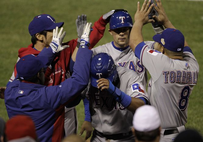 Texas Rangers' Elvis Andrus and Michael Young are congratulated in the dugout during the ninth inning of Game 2 of the World Series against the St. Louis Cardinals on Thursday, Oct. 20, 2011, in St. Louis. Andrus scored from third on a sacrifice fly by Young, as the Rangers won 2-1. (AP Photo/Paul Sancya)