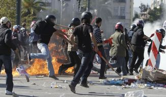 Communist-backed union protesters run from a firebomb hurled by other demonstrators in Athens on Thursday, Oct. 20, 2011. (AP Photo/Thanassis Stavrakis)