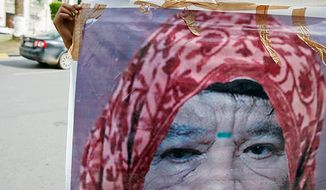 A Libyan man holds a photo of Col. Moammar Gadhafi, manipulated to show the leader dressed as a woman, in Tripoli, Libya, on Oct. 20, 2011. Libya's information minister said Gadhafi was killed earlier that day when revolutionary forces overwhelmed his hometown of Sirte. (Associated Press)