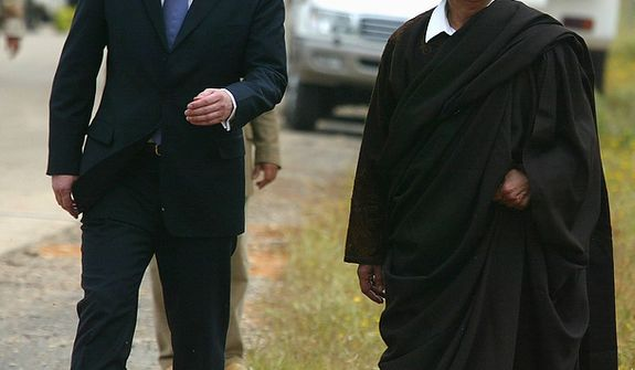 In this photo from March 25, 2004, Moammar Gadhafi (right) walks with Britain Prime Minister Tony Blair outside Tripoli, Libya. (Associated Press)