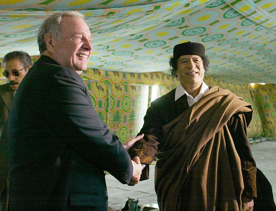 In this photo from Dec. 19, 2004, Canada Prime Minister Paul Martin shakes hands with Libyan leader Col. Moammar Gadhafi at his military compound in a tent in Tripoli, Libya. (Associated Press/The Canadian Press)