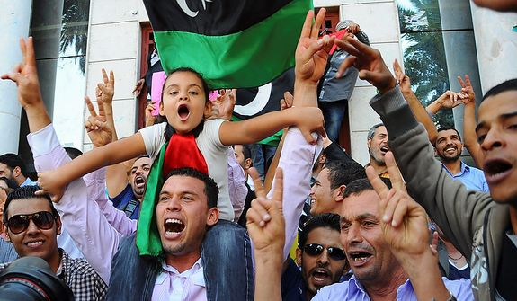 Libyans living in Tunisia celebrate outside the Libyan Embassy in Tunis on Oct. 20, 2011. Libya's information minister said Moammar Gadhafi was killed Thursday when revolutionary forces overwhelmed his hometown, Sirte, the last major bastion of resistance two months after the regime fell. (Associated Press)